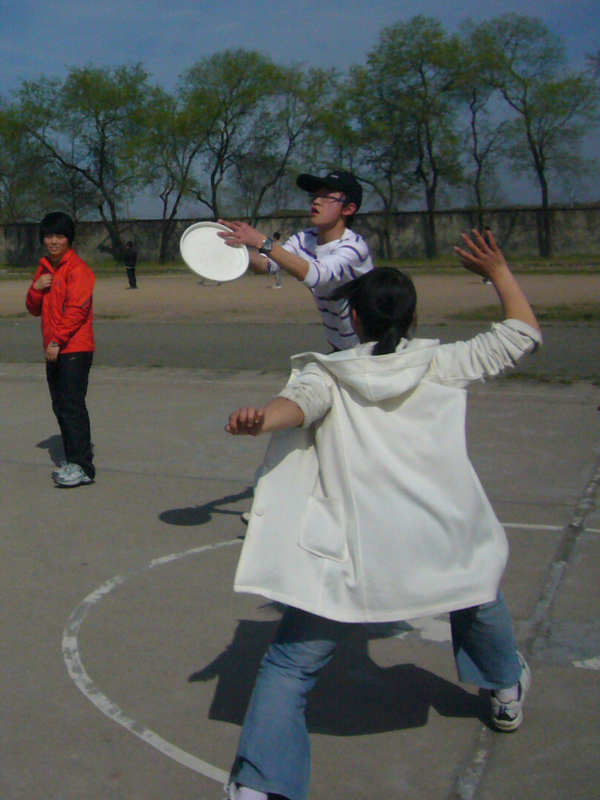 Senior 2 student Sonia guards James as he catches the Frisbee.
